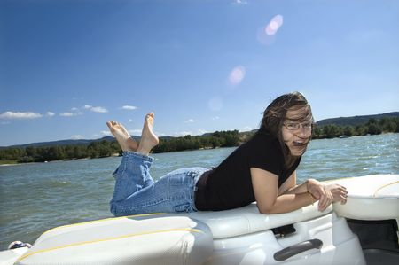 Happy smiling girl relaxing on a motorboat photo