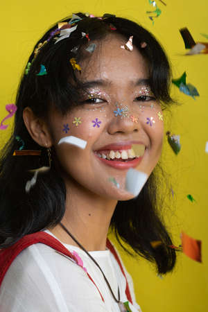 Beautiful young woman throwing confetti and looking happy on yellow background