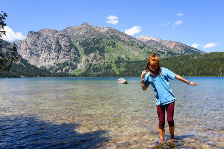 Red headed girl wading in clear mountain lake in summer