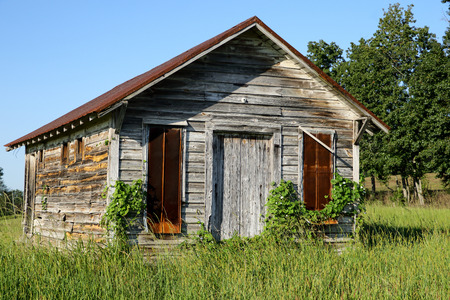 damaged roof: Old little weathered wood building with rusty metal roof in the summer