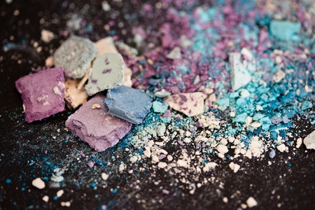 a still-life of colourful eyeshadow powder and make-up