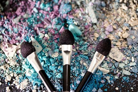 a still-life of colourful eyeshadow powder and make-up brushes photo