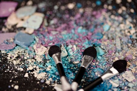 a still-life of colourful eyeshadow powder and make-up brushes