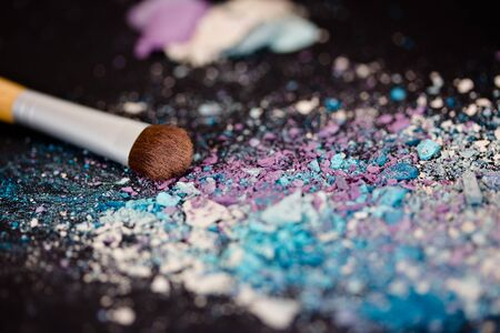 a still-life of colourful eyeshadow powder and make-up brush photo