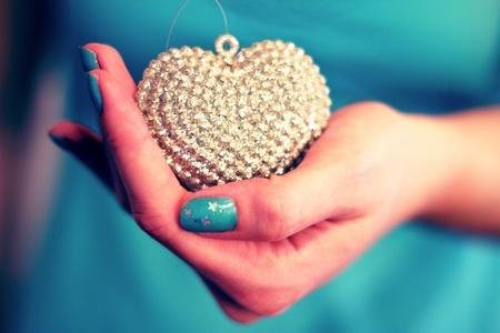 décoration des mains tenant coeur pailleté, bleu dof peu profond et vernis à ongles