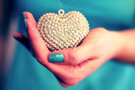 hands holding glittery heart decoration, blue nailpolish and shallow dof