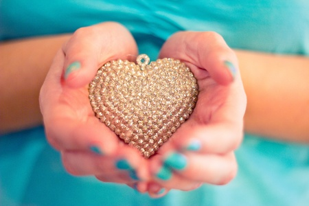 dof: hands holding glittery heart decoration, blue nailpolish and shallow dof