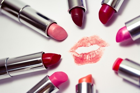 set of many colors of listicks in circle around lipstick kiss mark Stock Photo