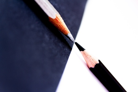 conceptual shot depicting contrast through black and white pencils facing each other