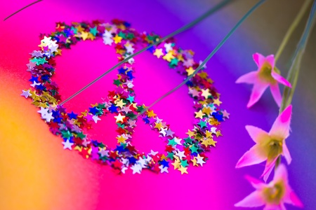 symbol of peace made up of colorful stars and with flowers photo