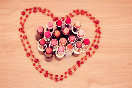 lipsticks colors with necklace in shape of heart photo