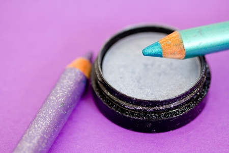 closeup of eyeliners and eyeshadow on purple photo