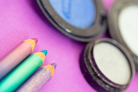 kohl: closeup of eyeliners and eyeshadows on purple