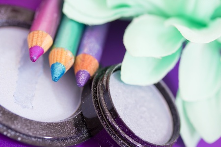 kohl: closeup of eyeliners and eyeshadows on purple with petals