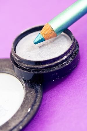 closeup of eyeliners and eyeshadows on purple photo