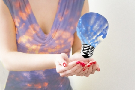 femal: femal hands holding lightbulb with clear sky