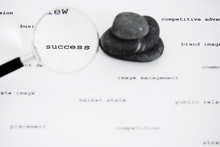 zen stones and magnifying glass focused on business words photo