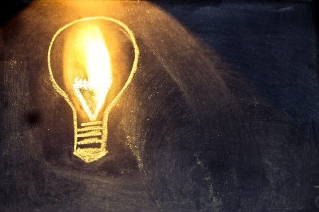 lighbulb design on blackboard, metaphor of innovation Stock Photo