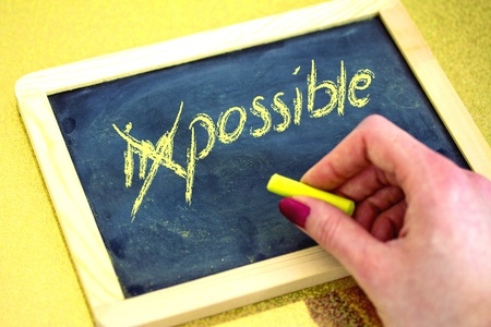 female hand writing on blackboard, impossible is possible Stock Photo - 17919955