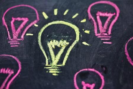 uniqueness: lighbulb design on blackboard representing uniqueness
