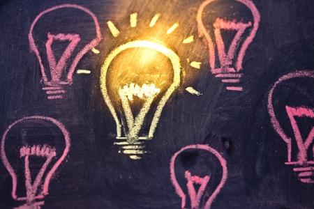 lighbulb design on blackboard representing uniqueness