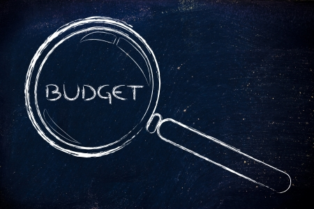 allocated: magnifying glass seeking proper budget in business Stock Photo