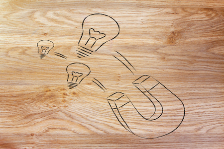funny magnet and lightbulb design, metaphor of attracting talents and ideas photo