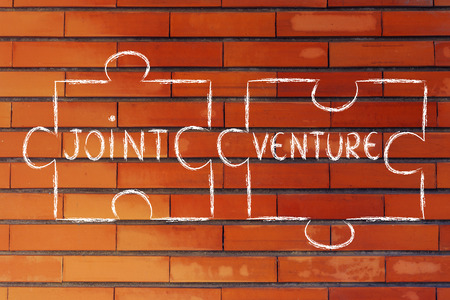 matching: the words Joint Venture written on 2 matching pieces of a jigsaw puzzle Stock Photo