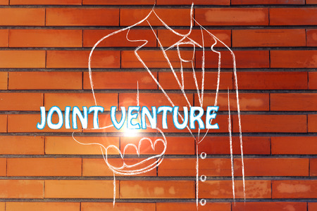 joint venture: business man holding the word Joint Venture