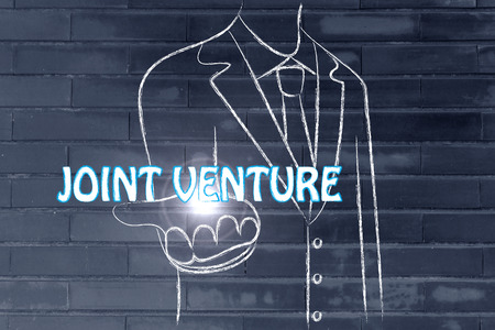 venture: business man holding the word Joint Venture