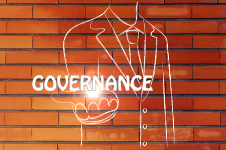 governance: business man holding the word Governance