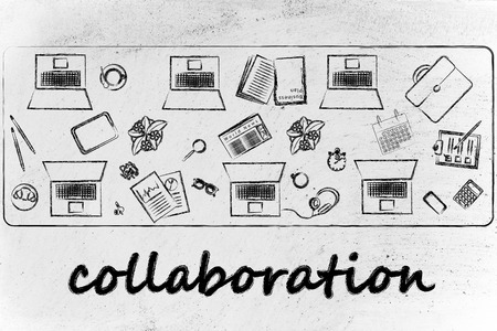 organizing and collaborating: laptops and office objects on shared desk photo