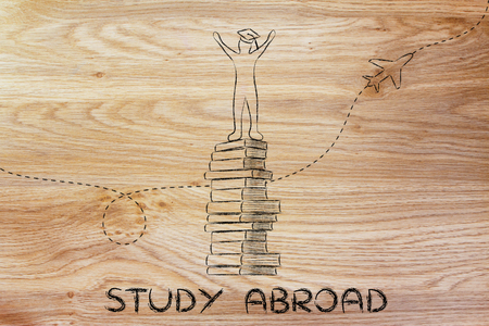 study abroad: happy graduated student on top of books with airplaine in the background Stock Photo