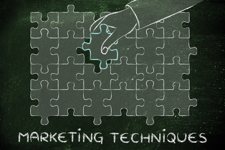 techniques: marketing techniques, hand about to add the missing piece to a jigsaw puzzle Stock Photo