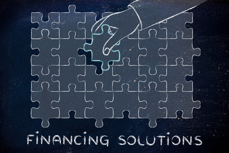 missing piece: financing solutions, hand about to add the missing piece to a jigsaw puzzle