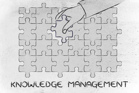 missing piece: knowledge management, metaphor of hand about to add the missing piece to a jigsaw puzzle