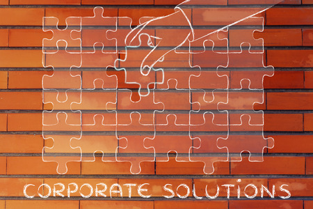 missing piece: corporate solutions, hand about to add the missing piece to a jigsaw puzzle