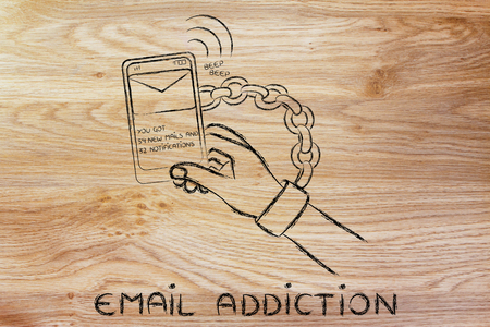distraction: hand chained to a beeping mobile phone, concept of addiction to checking emails