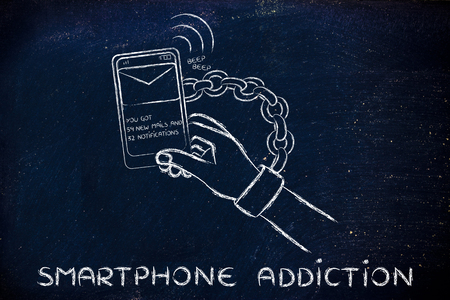 beeping: hand chained to a beeping mobile phone, concept of smartphone addiction