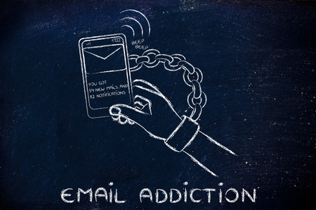 dependance: hand chained to a beeping mobile phone, concept of addiction to checking emails