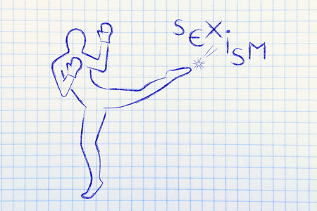 beings: fight against negative concepts: person kicking away the word sexism Stock Photo