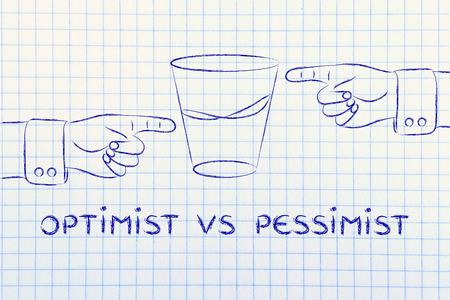 optimist vs pessimist: hands pointing at half full and half empty sides of glass of water