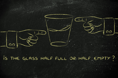 glass half full: is the glass half full or half empty: hands pointing from opposite point of views