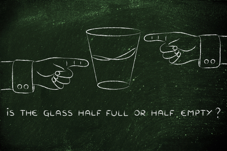 unhappiness: is the glass half full or half empty: hands pointing from opposite point of views