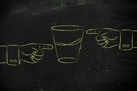 glass half full: contrasting point of views: hands pointing at glass to show its half full and half empty sides