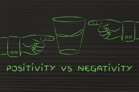 unhappiness: positivity vs negativity: hands pointing at half full and half empty sides of glass of water Stock Photo