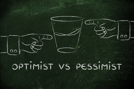glass half full: optimist vs pessimist: hands pointing at half full and half empty sides of glass of water