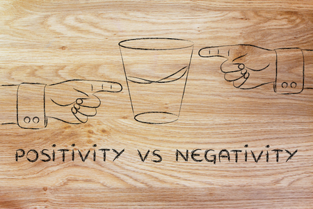half full: positivity vs negativity: hands pointing at half full and half empty sides of glass of water Stock Photo
