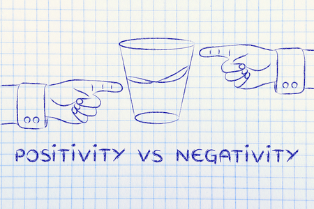 glass half full: positivity vs negativity: hands pointing at half full and half empty sides of glass of water Stock Photo