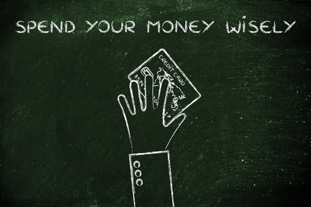 spending money: concept of spending money wisely: hand holding credit card